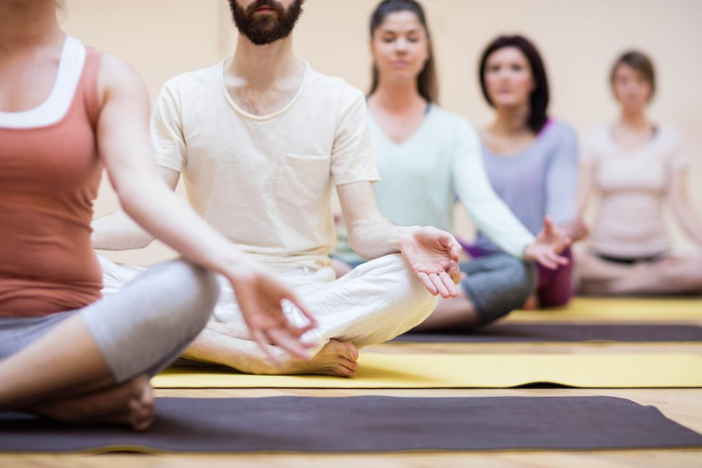 Group of people sitting in lotus position in the fitness studio